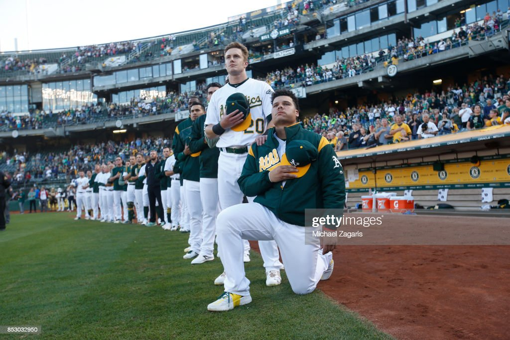 Bruce Maxwell #13 (R) of the Oakland Athletics kneels during the national anthem prior to the game against the Texas Rangers at the Oakland Alameda Coliseum on September 23, 2017 in Oakland, California. The Athletics defeated the Rangers 1-0.