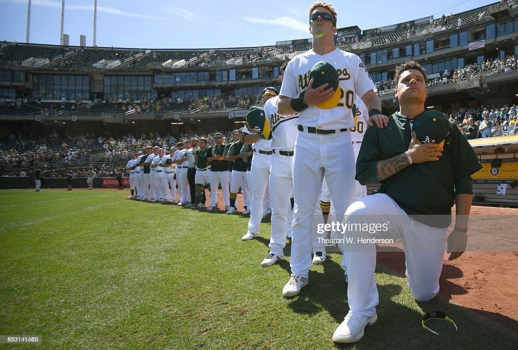Bruce Maxwell #13 of the Oakland Athletics kneels in protest next to teammate Mark Canha #20 duing the singing of the National Anthem prior to the start of the game against the Texas Rangers at Oakland Alameda Coliseum on September 24, 2017 in Oakland, California.