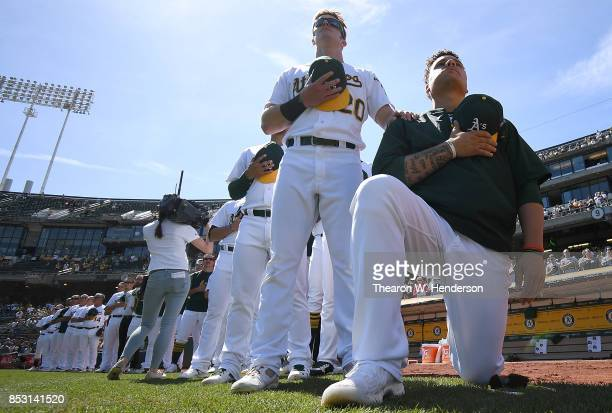 Bruce Maxwell of the Oakland Athletics kneels in protest next to teammate Mark Canha duing the singing of the National Anthem prior to the start of...