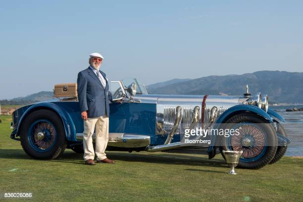 Bruce McCaw stands for a photograph next to his 1929 MercedesBenz S Barker Tourer after winning the Best of Show award during the 2017 Pebble Beach...