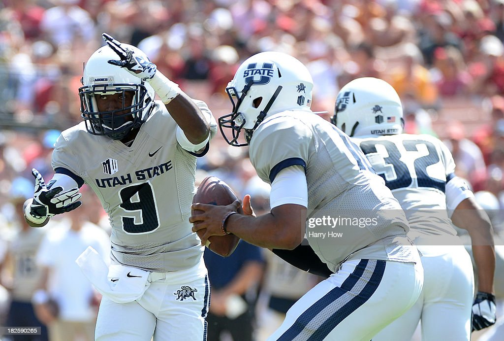Bruce Natson #9 of the Utah State Aggies fakes a handoff from Chuckie Keeton #16 during the game against the USC Trojans at the Los Angeles Memorial Coliseum on September 21, 2013 in Los Angeles, California.