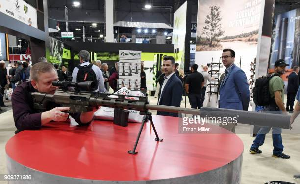 Bruce Nemec of Montana looks at a Bushmaster BA50 bolt action rifle at the Remington booth at the 2018 National Shooting Sports Foundation's Shooting...