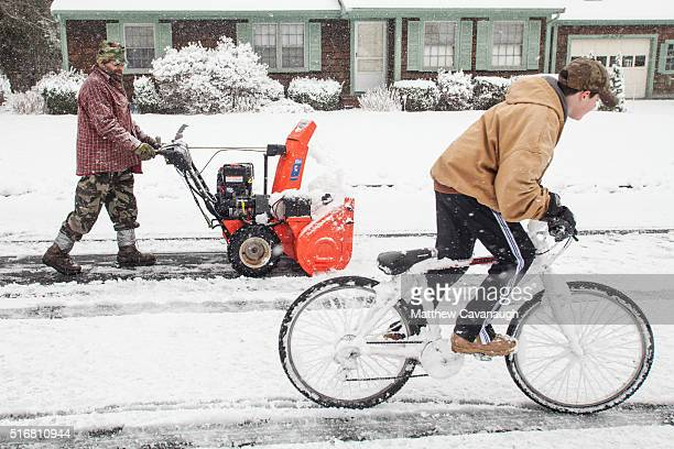 Bruce Price pushes a snowblower down Russell Ave as his young neighbor Landon Cluff rides past on a bicycle on March 21 2016 in Plymouth...
