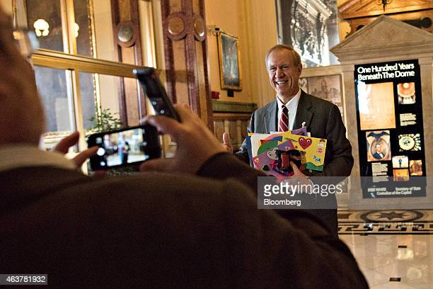 Bruce Rauner governor of Illinois right stands for a photograph while returning to his office at the Illinois State Capitol after delivering a budget...