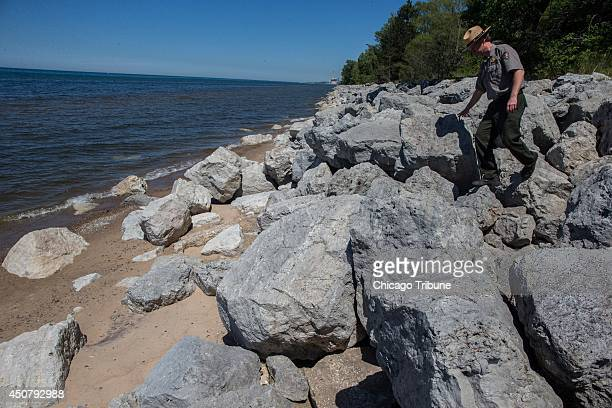 Bruce Rowe park ranger with the National Park Service walks down on a riprap built to prevent beach erosion at the Indiana Dunes National Lakeshore...