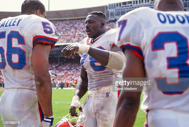 Bruce Smith #78 of the Buffalo Bills talks with his teammates Darryl Talley and Nate Odomes on the sidelines during a National Football League game...
