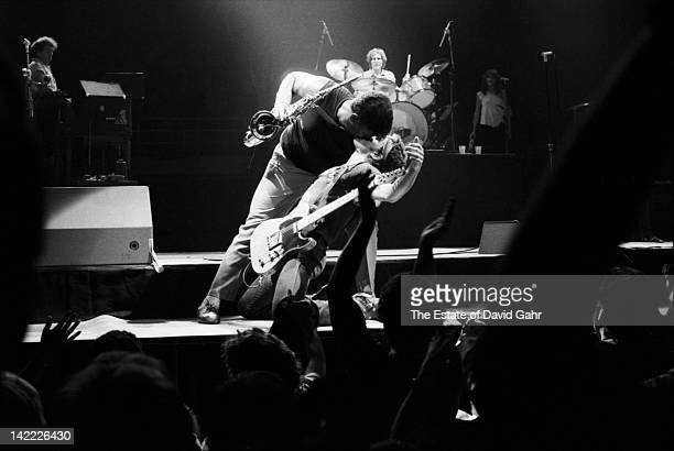 Bruce Springsteen and saxman Clarence Clemons stage kiss during performance in July 1984 at the Joe Louis Arena in Detroit Michigan
