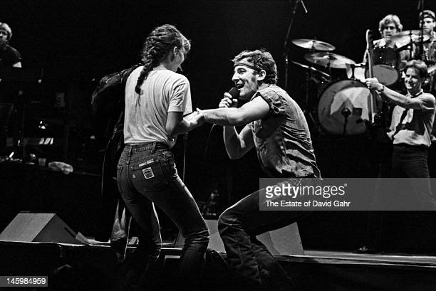 Bruce Springsteen dances with a fan on stage in July 1984 at the Joe Louis Arena in Detroit Michigan