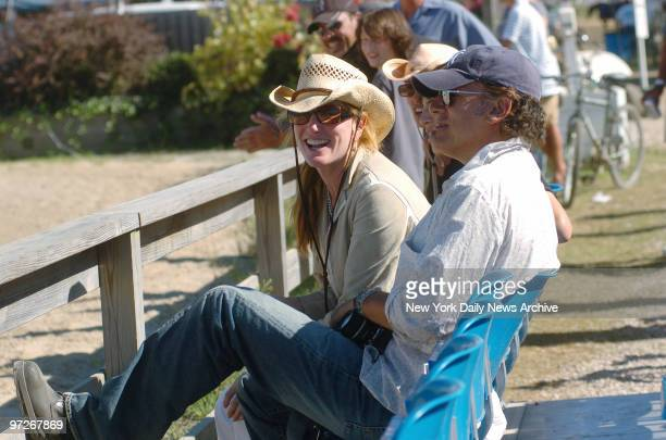 Bruce Springsteen toting a camera and wife Patti Scialfa watch from the stands as their daughter Jessica Springsteen competes at the 30th annual...