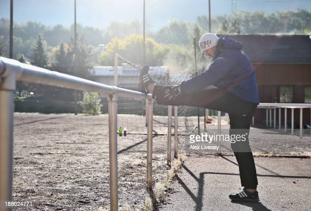 Bruce Tasker of the Great Britain bobsleigh team stretches prior to a push track training session on October 18 2013 in La Plagne France