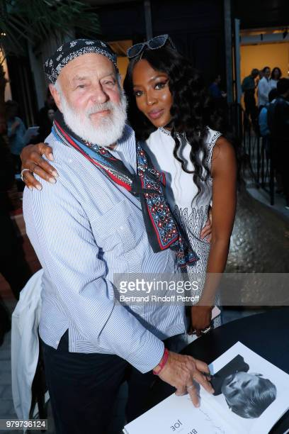 Bruce Weber signs the book for model Naomi Campbell during photographer Bruce Weber signs the book 'Azzedine Bruce and Joe' at Galerie Azzedine Alaia...