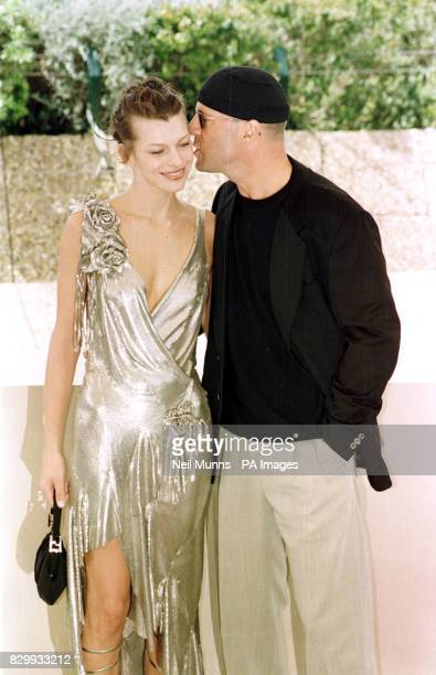 Bruce Willis gives Milla Jovovich a peck on the cheek during this photocall 'The Fifth Element' which Premieres tonight during the 50th Cannes Film...