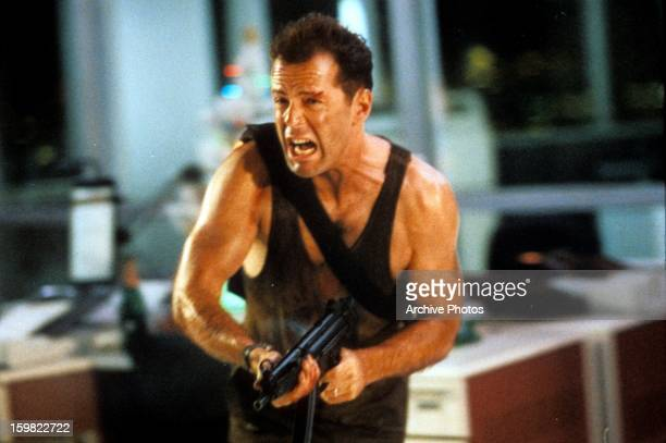 Bruce Willis running with automatic weapon in a scene from the film 'Die Hard' 1988
