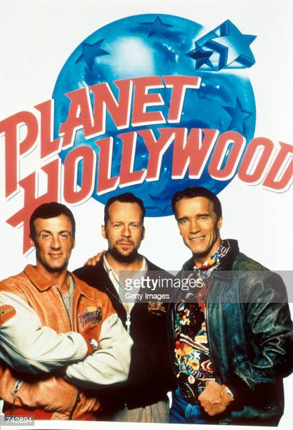 Bruce Willis Sylvester Stallone and Arnold Schwarzenegger pose with a Planet Hollywood poster in the background