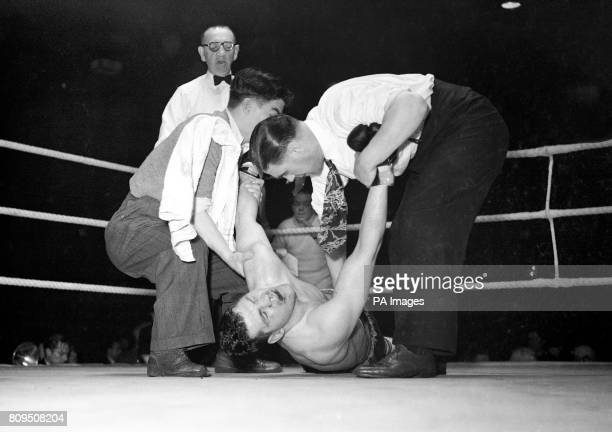 Bruce Woodcock is lifted to his corner by his brother Billy and manager Tom Hurst after Lee Savold's foul blow Savold used a 'below the belt' hit and...
