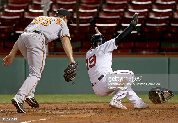 Bruce Zimmermann of the Baltimore Orioles misses the tag on Jackie Bradley Jr. #19 of the Boston Red Sox scores after taking advantage of a wild...