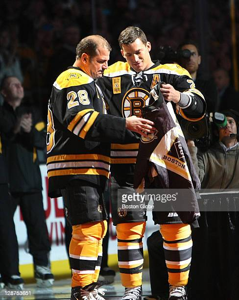 Bruins Andrew Ference presents retired Bruin Mark Recchi his lucky jacket