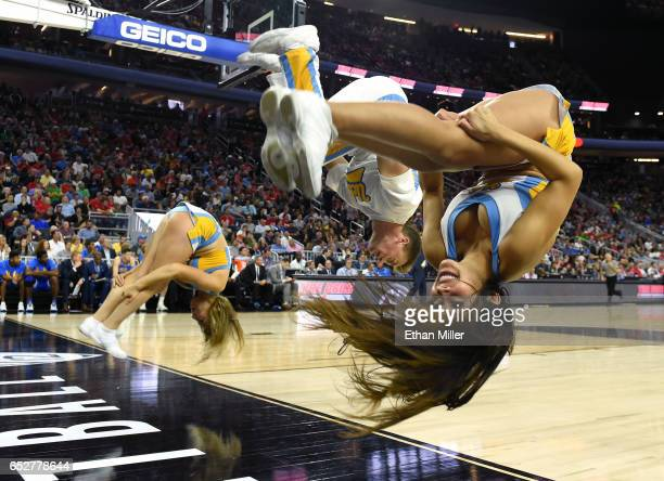 Bruins cheerleaders do backflips during the team's semifinal game of the Pac12 Basketball Tournament against the Arizona Wildcats at TMobile Arena on...