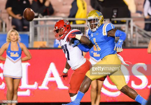 Bruins defensive back Darnay Holmes knocks the ball loose from Arizona Wildcats running back JJ Taylor during the game between Arizona and UCLA on...