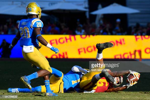 Bruins defensive back Darnay Holmes tackles USC Trojans wide receiver Michael Pittman Jr after a catch during a college football game between the...