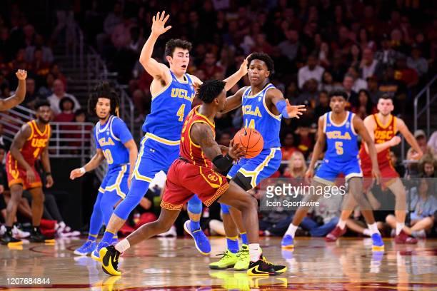 Bruins forward Jaime Jaquez Jr and UCLA Bruins guard David Singleton closely defend USC Trojans guard Jonah Mathews during the college basketball...