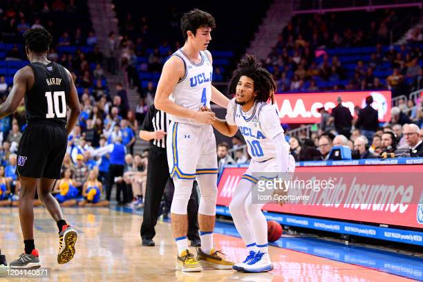 Bruins forward Jaime Jaquez Jr helps up UCLA Bruins guard Tyger Campbell during the game between the Washington Huskies and the UCLA Bruins on...