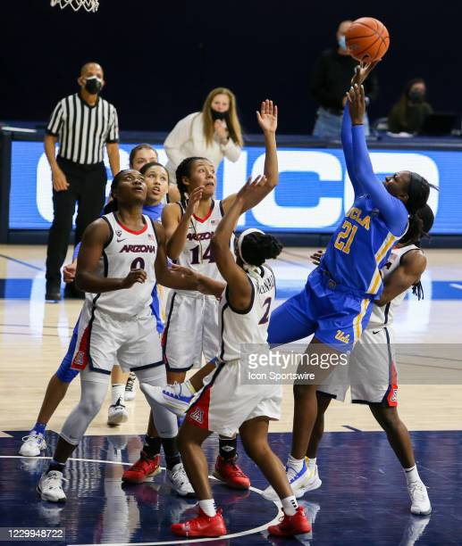 Bruins forward Michaela Onyenwere shoots the ball over Arizona Wildcats defenders during a college women's basketball game between the UCLA Bruins...