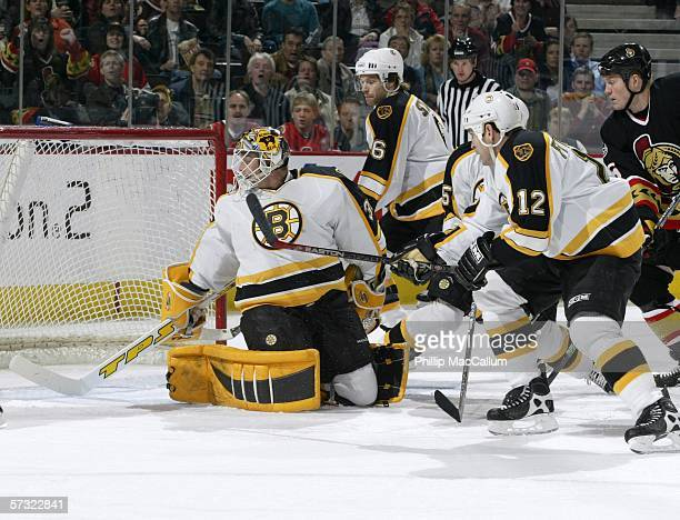 Bruins goaltender Tim Thomas Brad Stuart and Tom Fitzgerald watch a rebound go wide during the first period on April 11 2006 at the Scotiabank Place...