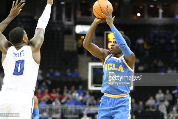 Bruins guard Aaron Holiday shoots over Creighton Bluejays guard Marcus Foster in the first half of the semifinal game of the CBE Hall of Fame Classic...