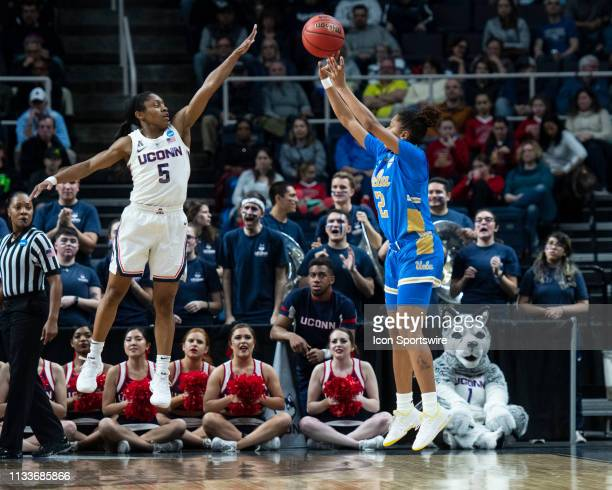 Bruins Guard Ahlana Smith shoots a three point jump shot with Connecticut Huskies Guard Crystal Dangerfield defending during the first half of the...