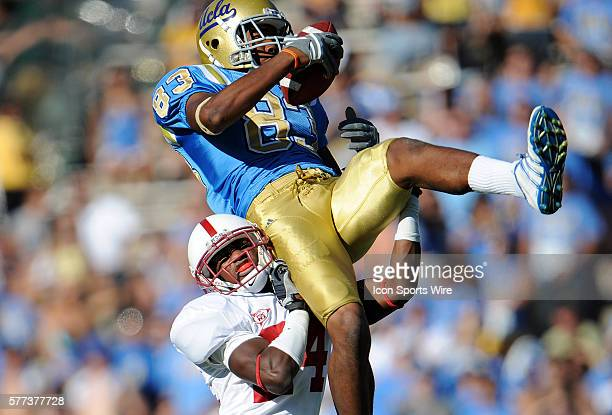 Bruins Nelson Rosario is hit into the air after making a catch against Kris Evans during a college football game between the Stanford Cardinals and...