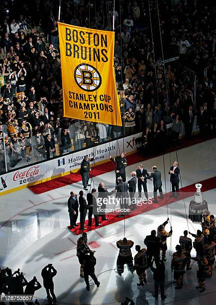 Bruins players and executives raise the Championship Banner with the Stanley Cup at far right The Boston Bruins opened up the 201112 NHL regular...