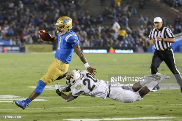 Bruins quarterback Dorian ThompsonRobinson slips put of Colorado Buffaloes linebacker Davion Taylor grasp during the college football game between...