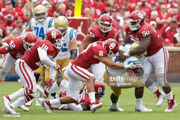 Bruins running back Bolu Olorunfunmi is tacked by Oklahoma Sooners safety Kahlil Haughton and defensive lineman Neville Gallimore during the UCLA...