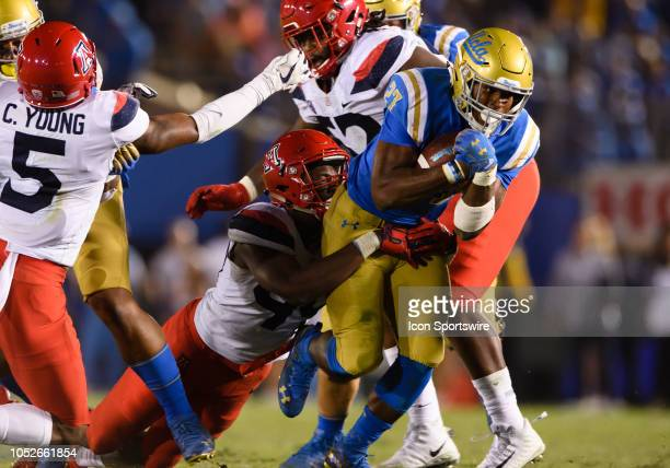 Bruins running back Joshua Kelley carries the ball as Arizona Wildcats defensive end Jalen Harris hangs on during the game between Arizona and UCLA...