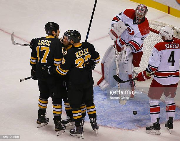 Bruins Seth Griffithis congratulated by Milan Lucic left and Chris Kelly after his first period unassisted goal past Carolina goalie Cam Ward The...