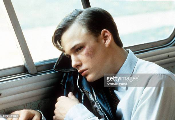 Bruised Brad Renfro leaning head against bus window in a scene from the film 'Telling Lies In America' 1997