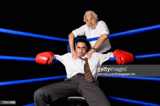 Bruised businessman sitting in corner of boxing ring with coach