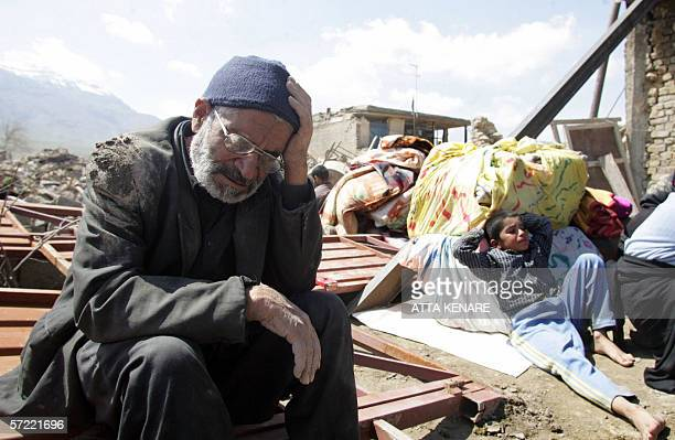 Members of an Iranian family sit amid debris in Khaleq Ali village near the city of Brujerd following a powerful earthquake which struck western Iran...