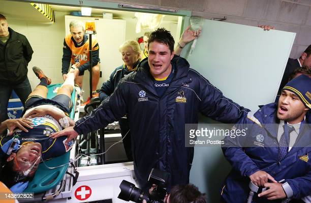 Brumbies players gather around injured Chirstian Lealiifano to sing the team song during the round 11 Super Rugby match between the Brumbies and the...