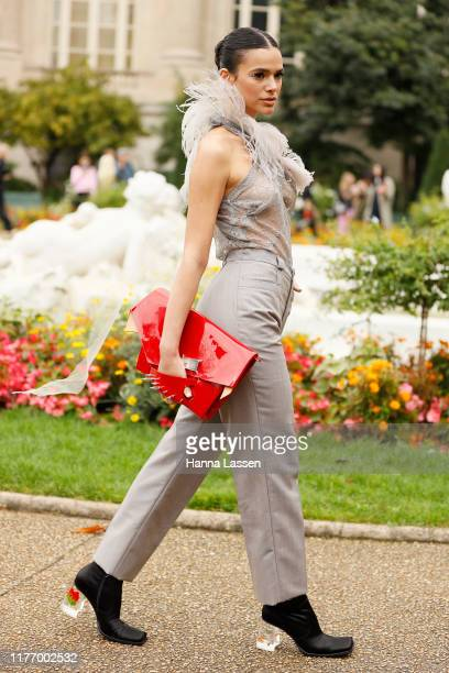 Bruna Marquezine wearing feather detailed see through top light grey pants and red patent clutch outside Maison Margiela on September 25 2019 in...