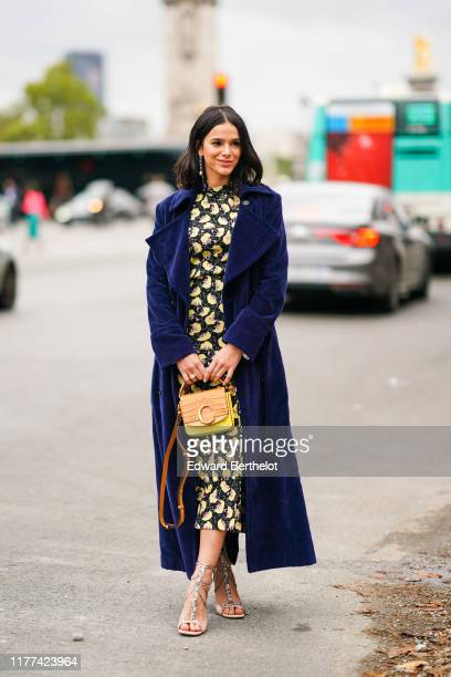 Bruna Marquezine wears a blue long coat a yellow and black floral print dress a yellow and orange Chloe bag high heeled shoes outside Chloe during...