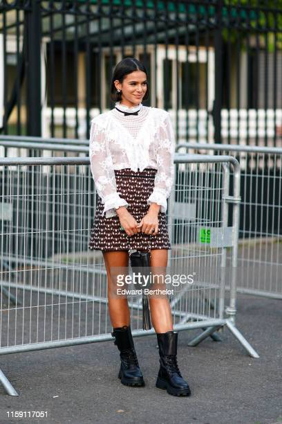 Bruna Marquezine wears earrings, a white lace embroidered top, a skirt, a balck bag with fringes, black boots, a small bow tie, outside Miu Miu Club...