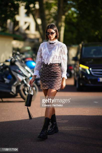 Bruna Marquezine wears earrings a white lace embroidered top a skirt a balck bag with fringes black boots a small bow tie outside Miu Miu Club 2020...