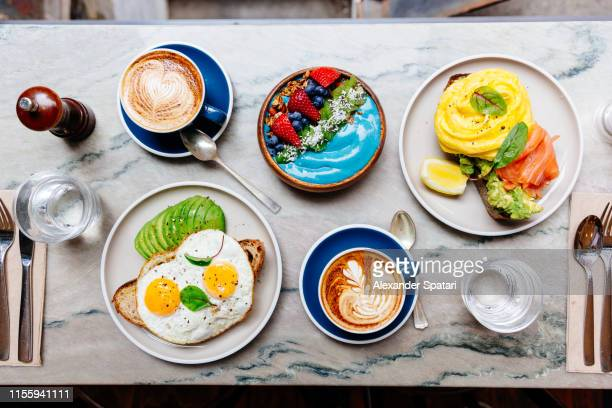 brunch at cafe with avocado toast, fried and scrambled egg, salmon, smoothie bowl and coffee - prima colazione foto e immagini stock