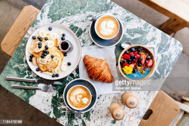 brunch at the cafe with smoothie bowl, ricotta pancakes, croissant and cappuccino, directly above view - acai stock pictures, royalty-free photos & images