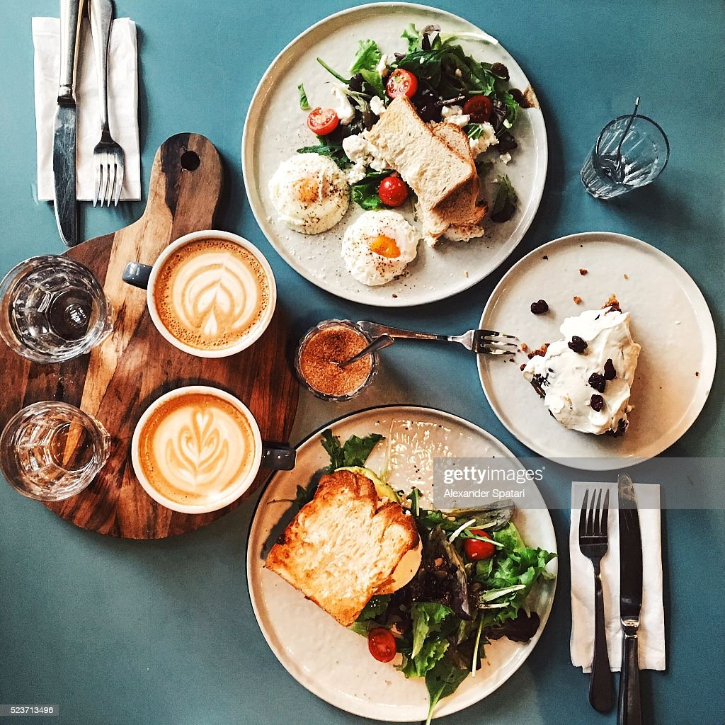 Brunch for two people with avocado toast, fried egg, salad, cappuccino and carrot cake served on the table, high angle view : Stock Photo