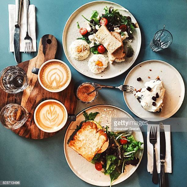 brunch for two people with avocado toast, fried egg, salad, cappuccino and carrot cake served on the table, high angle view - avocado toast stockfoto's en -beelden