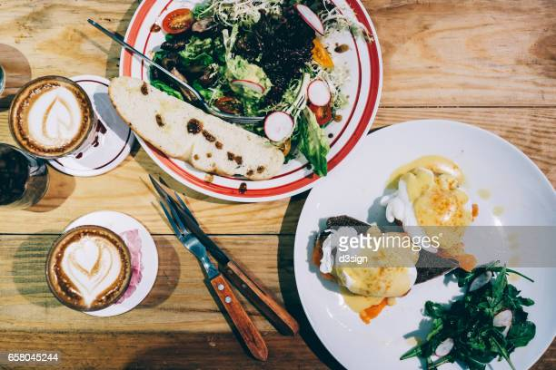 Brunch for two people with egg benedict and mixed greens and coffee freshly served on the table