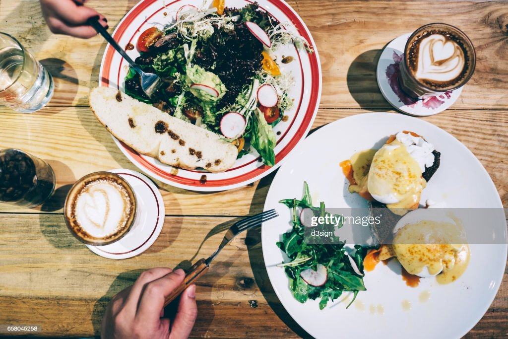 Brunch for two people with egg benedict and mixed greens and coffee freshly served on the table : Stock Photo